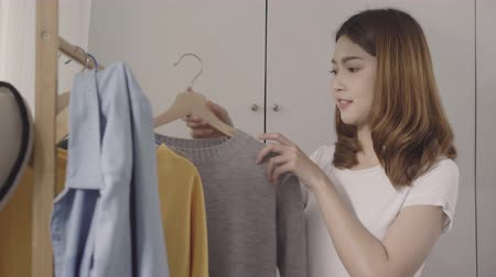 decisões : Beautiful attractive young Asian woman choosing her fashion outfit clothes in closet at home or store. Girl think what to wear sweater. Home wardrobe or clothing shop changing room.