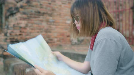 сумки : Traveler Asian woman direction and looking on location map while spending holiday trip at Ayutthaya, Thailand, backpacker female enjoy journey in traditional city. Lifestyle women travel concept.