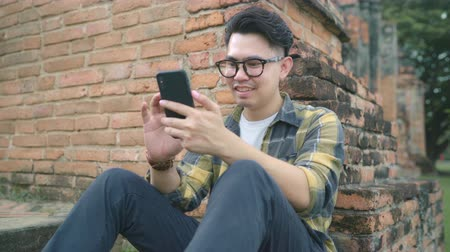Аюттхая : Traveler Asian man using smartphone checking social media while relax after spending holiday trip at Ayutthaya, Thailand, Male enjoy his journey at amazing landmark in traditional city.