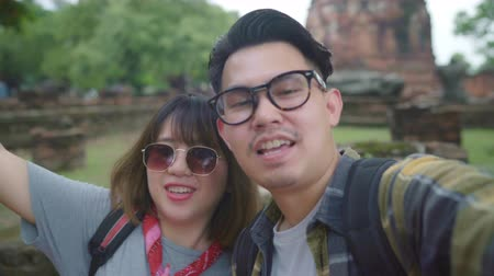 tomar : Traveler Asian couple using smartphone taking selfie while spending holiday trip at Ayutthaya, Thailand, Couple enjoy their journey at amazing landmark in traditional city.