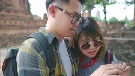 Аюттхая : Traveler Asian couple using smartphone for direction and looking on location map while spending holiday trip at Ayutthaya, Thailand, backpacker sweet couple enjoy journey in traditional city.