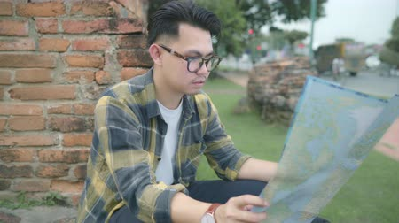 gençlik kültürü : Traveler Asian man direction and looking on location map while spending holiday trip at Ayutthaya, Thailand, backpacker male enjoy journey in traditional city. Lifestyle men travel concept. Stok Video