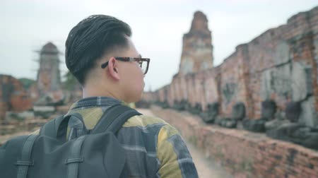 bolsa : Traveler Asian man spending holiday trip at Ayutthaya, Thailand, backpacker male enjoy his journey at amazing landmark in traditional city. Lifestyle men travel holidays concept.