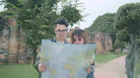Аюттхая : Traveler Asian couple direction and looking on location map while spending holiday trip at Ayutthaya, Thailand, backpacker couple enjoy journey in traditional city. Lifestyle couple travel concept.