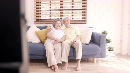 nagymama : Asian elderly couple using tablet watching TV in living room at home, couple enjoy love moment while lying on sofa when relaxed at home. Enjoying time lifestyle senior family at home concept. Stock mozgókép