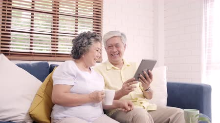 senior lifestyle : Asian elderly couple using tablet and drinking coffee in living room at home, couple enjoy love moment while lying on sofa when relaxed at home. Enjoying time lifestyle senior family at home concept. Stock Footage