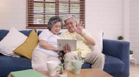 descontraído : Asian elderly couple using tablet watching TV in living room at home, couple enjoy love moment while lying on sofa when relaxed at home. Enjoying time lifestyle senior family at home concept. Vídeos