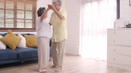 objetí : Asian elderly couple dancing together while listen to music in living room at home, sweet couple enjoy love moment while having fun when relaxed at home. Lifestyle senior family relax at home concept.