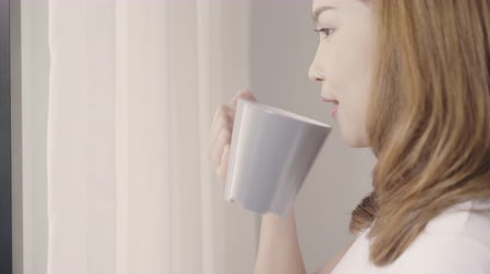 desperto : Happy beautiful Asian woman smiling and drinking a cup of coffee or tea near the window in the bedroom. Young asian female open the curtains and relax in the morning. Lifestyle woman at home concept. Stock Footage