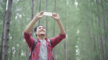 写真 : Hiker Asia backpacker man using smartphone for take a picture while on hiking adventure walking in forest, Asian male enjoy his holidays near lots of tree. Lifestyle men travel and relax concept.