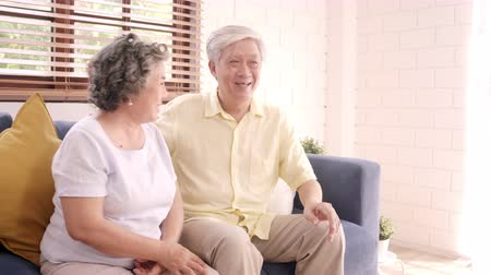 nagymama : Asian elderly couple watching television in living room at home, sweet couple enjoy love moment while lying on the sofa when relaxed at home. Enjoying time lifestyle senior family at home concept.