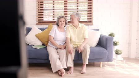descontraído : Asian elderly couple watching television in living room at home, sweet couple enjoy love moment while lying on the sofa when relaxed at home. Enjoying time lifestyle senior family at home concept.