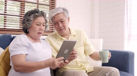 descontraído : Asian elderly couple using tablet and drinking coffee in living room at home, couple enjoy love moment while lying on sofa when relaxed at home. Enjoying time lifestyle senior family at home concept. Vídeos