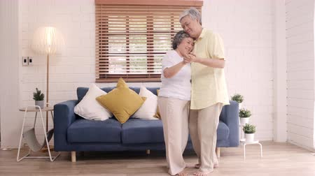 nagymama : Asian elderly couple dancing together while listen to music in living room at home, sweet couple enjoy love moment while having fun when relaxed at home. Lifestyle senior family relax at home concept.