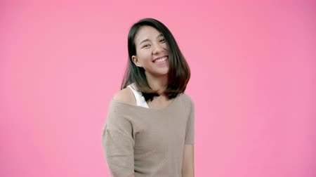 torcendo : Smiling adorable Asian female with positive expression, smiles broadly, dressed in casual clothing and looking at the camera over pink background. Happy adorable glad woman rejoices success.
