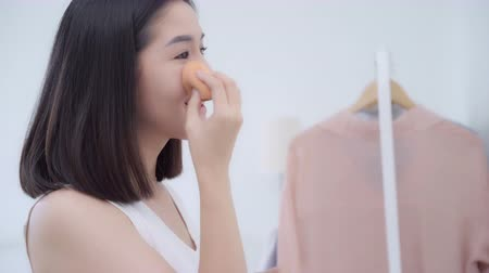 javul : Beautiful Asian woman using powder make up in front mirror, Happy female using beauty cosmetics to improve herself ready to working in bedroom at home. Lifestyle women relax at home concept.