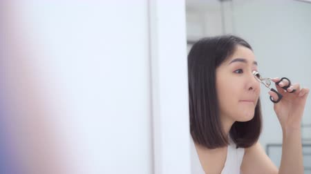 tusz do rzęs : Beautiful Asian woman using eyelash curler makeup in front mirror, Happy female using beauty cosmetics to improve herself ready to working in bedroom at home. Lifestyle women relax at home concept.