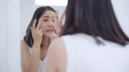 щеткой : Beautiful Asian woman using eyeshadow makeup in front mirror, Happy female using beauty cosmetics to improve herself ready to working in bedroom at home. Lifestyle women relax at home concept.
