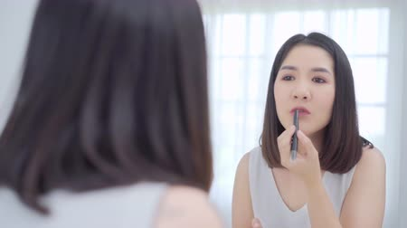 make up : Beautiful Asian woman using lipstick make up in front mirror, Happy female using beauty cosmetics to improve herself ready to working in bedroom at home. Lifestyle women relax at home concept.