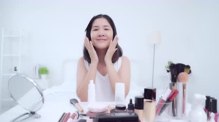 щеткой : Beauty blogger present beauty cosmetics sitting in front camera for recording video. Happy beautiful young Asian woman use cosmetics review make up tutorial broadcast live video to social network.