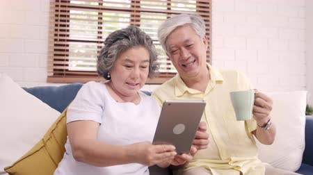 pensão : Asian elderly couple using tablet and drinking coffee in living room at home, couple enjoy love moment while lying on sofa when relaxed at home. Enjoying time lifestyle senior family at home concept. Vídeos