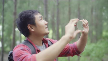 zálesí : Hiker Asia backpacker man using smartphone for take a picture while on hiking adventure walking in forest, Asian male enjoy his holidays near lots of tree. Lifestyle men travel and relax concept.
