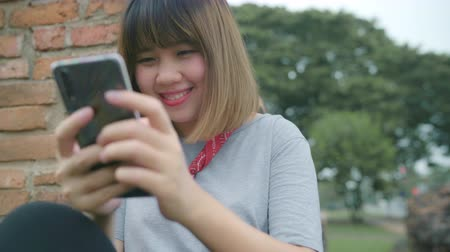 Аюттхая : Traveler Asian woman using smartphone checking social media while relax after spending holiday trip at Ayutthaya, Thailand, female enjoy her journey at amazing landmark in traditional city.