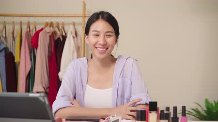 revisão : Beauty blogger present beauty cosmetics sitting in front tablet for recording video. Happy beautiful young Asian woman use cosmetics review make up tutorial broadcast live video to social network.