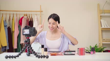 revisão : Beauty blogger present beauty cosmetics sitting in front camera for recording video. Happy beautiful young Asian woman use cosmetics review make up tutorial broadcast live video to social network.