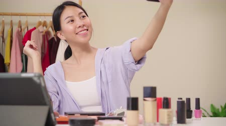 make up : Happy beautiful young Asian woman using smartphone selfie live streaming online to social network. Beauty blogger present beauty cosmetics sitting in front tablet camera for recording video.
