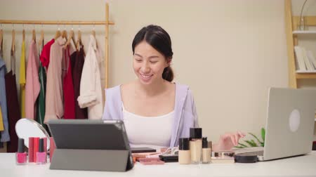perguntando : Beauty blogger question and answer by laptop sitting in front tablet for recording video. Happy beautiful young Asian woman use cosmetics review make up tutorial broadcast live video to social network Stock Footage