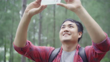 přežití : Hiker Asia backpacker man using smartphone for take a picture while on hiking adventure walking in forest, Asian male enjoy his holidays near lots of tree. Lifestyle men travel and relax concept.