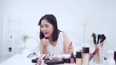 difundir : Beauty blogger present beauty cosmetics sitting in front camera for recording video. Happy beautiful young Asian woman use cosmetics review make up tutorial broadcast live video to social network.