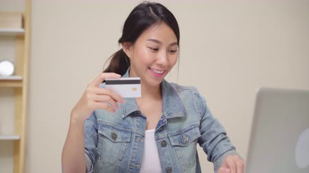 pátek : Beautiful Asian woman using laptop buying online shopping by credit card while wear casual sitting on desk in living room at home. Lifestyle women working at home concept. Dostupné videozáznamy