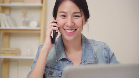 стремление : Beautiful smart business Asian woman in smart casual wear working on laptop and talking on phone while sitting on table in creative office. Lifestyle women working at home concept.