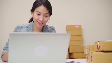 rád : Beautiful smart Asian young entrepreneur business woman owner of SME online checking product on stock and save to computer working at home. Small business owner at home office concept.