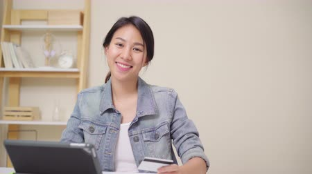 rád : Beautiful Asian woman using tablet buying online shopping by credit card while wear casual sitting on desk in living room at home. Lifestyle women working at home concept.