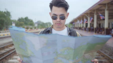 сумки : Traveler Asian man direction and looking on location map while spending holiday trip and waiting train at train station, Young male tourist backpacker enjoy journey. Lifestyle men travel concept.