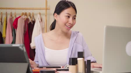revisão : Beauty blogger question and answer by laptop sitting in front tablet for recording video. Happy beautiful young Asian woman use cosmetics review make up tutorial broadcast live video to social network Stock Footage