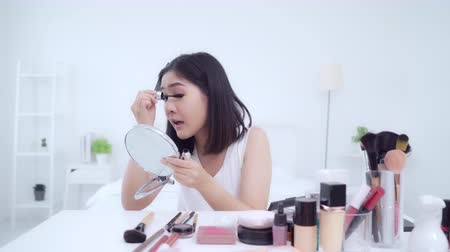 viral : Beauty blogger present beauty cosmetics sitting in front camera for recording video. Happy beautiful young Asian woman use cosmetics review make up tutorial broadcast live video to social network.