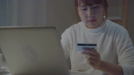 rád : Beautiful Asian woman using laptop buying online shopping by credit card while wear casual sitting on desk in living room in the night at home. Lifestyle women working at home office concept.