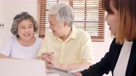 контракт : Asia smart female agent offers health insurance for elderly couples by document, tablet and laptop. Aged Asian couple consulting with insurance agent while sitting together with at home.