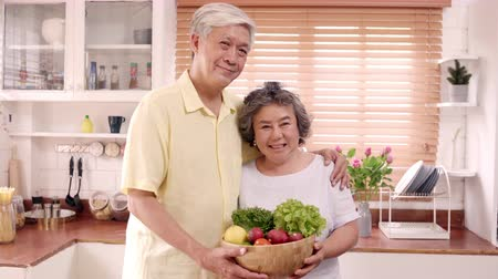 иероглиф : Asian elderly couple feeling happy smiling and holding fruit and looking to camera while relax in kitchen at home. Lifestyle Senior family enjoy time at home concept. Portrait looking at camera. Стоковые видеозаписи