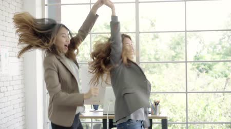 torcendo : Slow motion - Asian business women feeling happy enjoy and having fun dancing arms raised celebrating after hear success Operating Result in office. Lifestyle business working in workplace concept. Vídeos