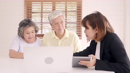 magánélet : Asia smart female agent offers health insurance for elderly couples by document, tablet and laptop. Aged Asian couple consulting with insurance agent while sitting together with at home.