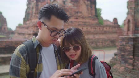 navigovat : Traveler Asian couple using smartphone for direction and looking on location map while spending holiday trip at Ayutthaya, Thailand, backpacker sweet couple enjoy journey in traditional city.