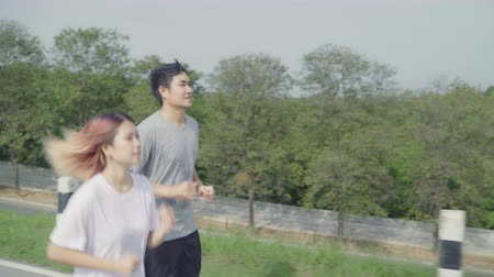 életerő : Asian runner couple running and jogging on street, Healthy young sporty sweet couple exercise near lake. Lifestyle fit and active couple exercise on street concept.
