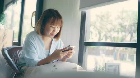 çay : Business freelance Asian woman using smartphone for talking, reading and texting while sitting on table in cafe. Lifestyle smart beautiful women working at coffee shop concepts.