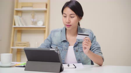 ispanico : Beautiful Asian woman using tablet buying online shopping by credit card while wear casual sitting on desk in living room at home. Lifestyle women working at home concept.
