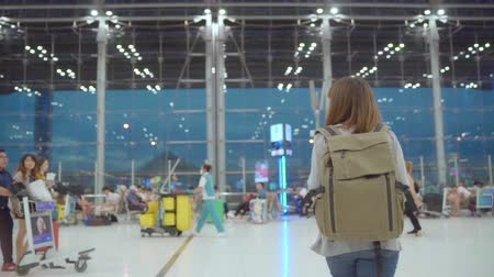 pas : Slow motion - Young Asian backpacker woman walking in terminal hall while going to boarding flight at the departure gate in international airport. Lifestyle backpack tourist travel holiday concept.